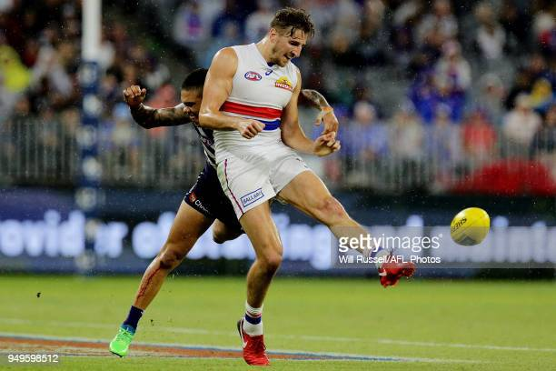 Marcus Bontempelli of the Bulldogs kicks the ball under pressure from Michael Walters of the Dockers during the round five AFL match between the...
