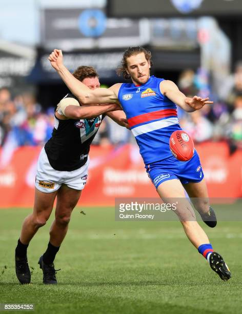 Marcus Bontempelli of the Bulldogs kicks whilst being tackled by Brad Ebert of the Power during the round 22 AFL match between the Western Bulldogs...