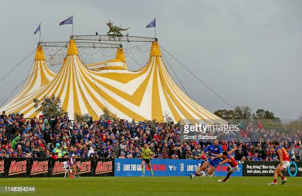 Marcus Bontempelli of the Bulldogs runs with the ball as the circus takes place next to the ground during the round eight AFL match between the...