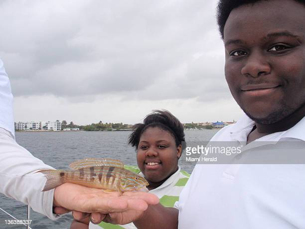 Marcus Butler and Janiqua Frederick pose with a small sand perch Butler caught in the Intracoastal Waterway during a rainy outing with the Florida...