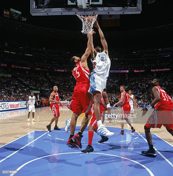 Marcus Camby of the Denver Nuggets goes to the basket against Juwan Howard of the Houston Rockets during a game at Pepsi Center on January 9 2005 in...