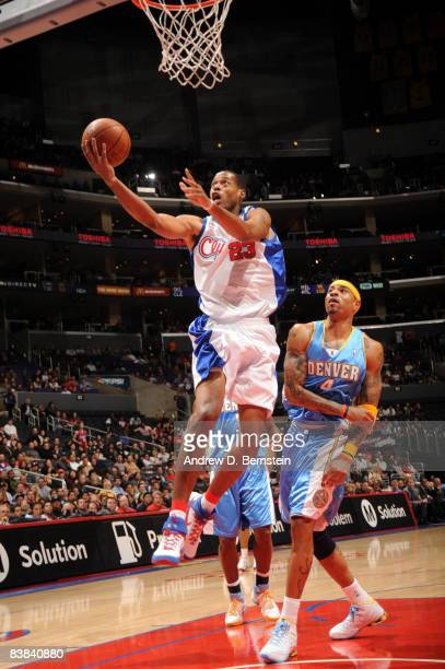 Marcus Camby of the Los Angeles Clippers goes up for a shot while Kenyon Martin of the Denver Nuggets looks on during their game at Staples Center on...