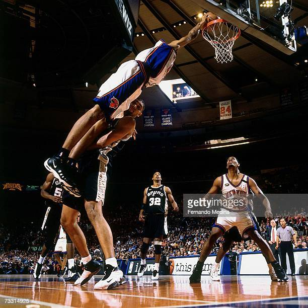 Marcus Camby of the New York Knicks slam dunks against Tim Duncan of the San Antonio Spurs during a game played in 1999 at Madison Square Garden in...