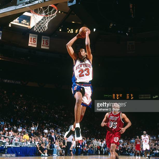 Marcus Camby of the New York Knicks takes the ball to the basket past Clarence Weatherspoon of the Miami Heat in Game Three of the Eastern Conference...