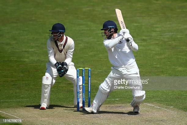 Marcus Campopiano of Sussex hits out while Surrey wicket keeper Billy Mead looks on during the Second Eleven Championship match between Sussex 2nd XI...