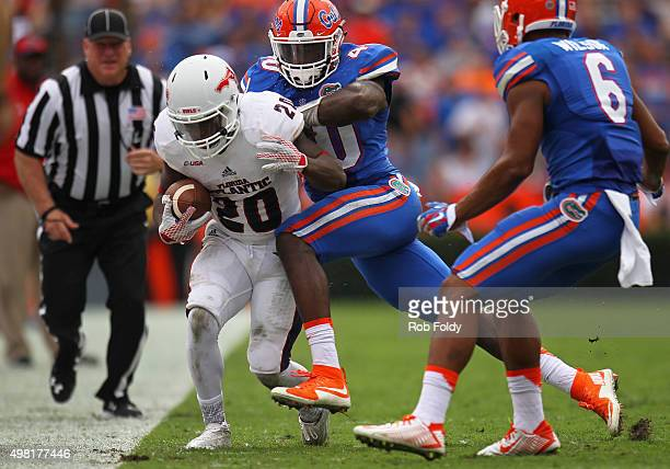 Marcus Clark of the Florida Atlantic Owls is knocked out of bounds by Jarrad Davis of the Florida Gators of the game at Ben Hill Griffin Stadium on...
