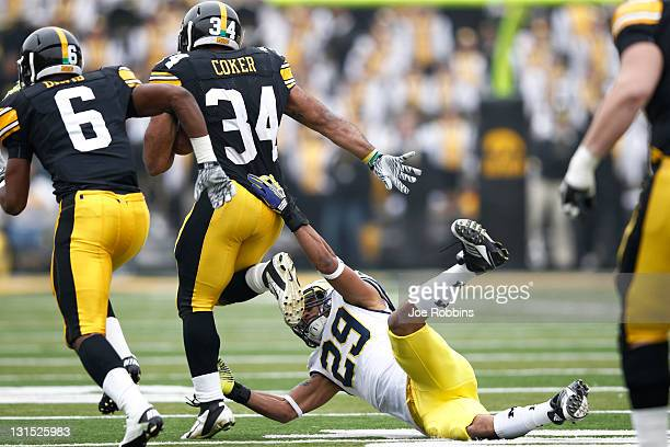 Marcus Coker of the Iowa Hawkeyes runs over Troy Woolfolk of the Michigan Wolverines during first half action at Kinnick Stadium on November 5 2011...