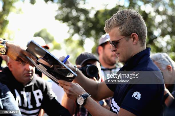 Marcus Ericsson of Sweden and Sauber F1 arrives at the circuit and signs autographs for fans during previews to the Australian Formula One Grand Prix...