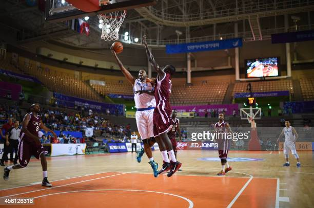 Marcus Eugene Douthit of the Philippines reaches for the basket against Erfan Alsi Saeed of Qatar during their men's quarterfinal basketball match of...