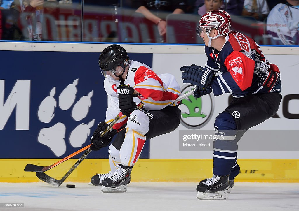 Marcus Fagerudd #5 of Lulea Hockey and Jerome Flaake #90 of Hamburg Freezers struggle for the puck during the Champions Hockey League group stage game between Hamburg Freezers and Lulea HF on August 22, 2014 in Hamburg, Germany.