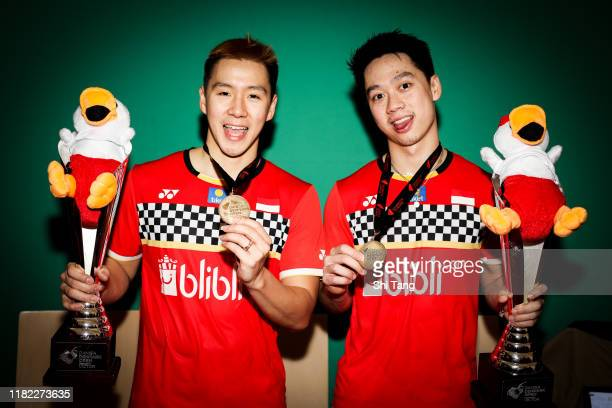 Marcus Fernaldi Gideon and Kevin Sanjaya Sukamuljo of Indonesia pose with their trophies after the Men's Double final match against Hendra Setiawan...