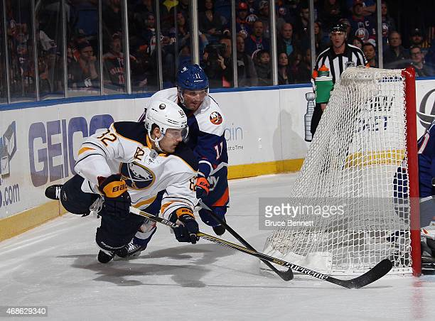 Marcus Foligno of the Buffalo Sabres attempts to wrap the puck arouund the net as he is tripped up by Lubomir Visnovsky of the New York Islanders...