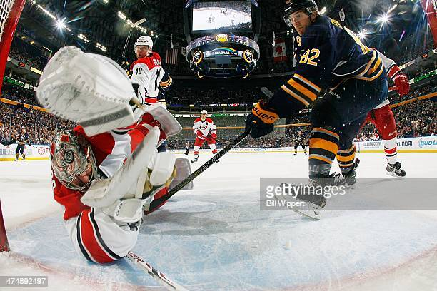 Marcus Foligno of the Buffalo Sabres charges into the crease as goaltender Cam Ward of the Carolina Hurricanes can't stop the puck for the...
