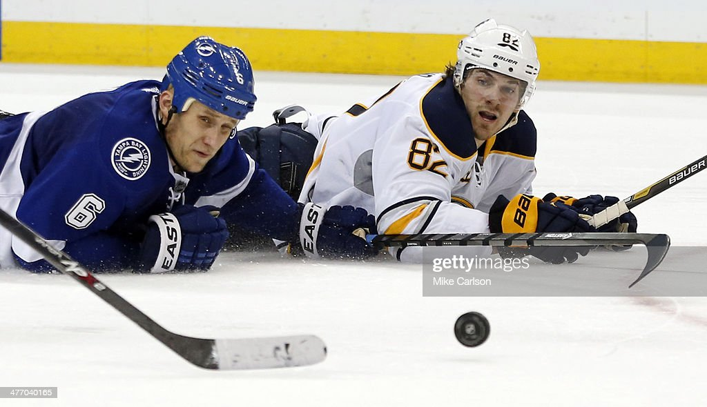 Marcus Foligno #82 of the Buffalo Sabres (R) chips the puck past Sami Salo #6 of the Tampa Bay Lightning for an assist on a goal by Cody Hodgson #19 at the Tampa Bay Times Forum on March 6, 2014 in Tampa, Florida.