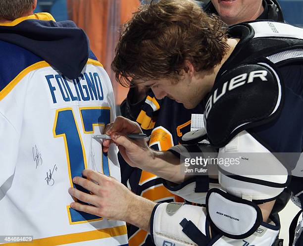Marcus Foligno of the Buffalo Sabres signs the jersey of a fan after playing the New York Islanders at First Niagara Center on April 13 2014 in...