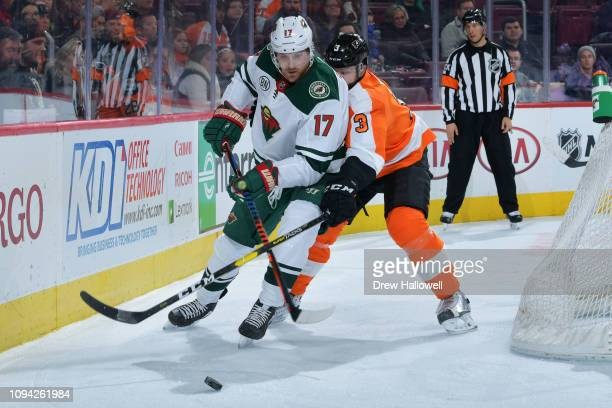 Marcus Foligno of the Minnesota Wild and Radko Gudas of the Philadelphia Flyers battle for the puck at Wells Fargo Center on January 14 2019 in...