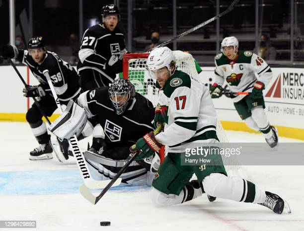 Marcus Foligno of the Minnesota Wild controls the puck from his knees in front of Jonathan Quick of the Los Angeles Kings during the first period in...