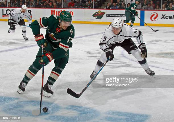 Marcus Foligno of the Minnesota Wild skates with the puck as Adrian Kempe of the Los Angeles Kings defends during a game between the Minnesota Wild...