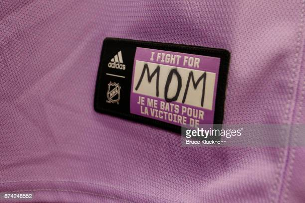 Marcus Foligno of the Minnesota Wild writes 'Mom' on his warmup lavender jersey as part of Hockey Fights Cancer Awareness Night prior to the game...