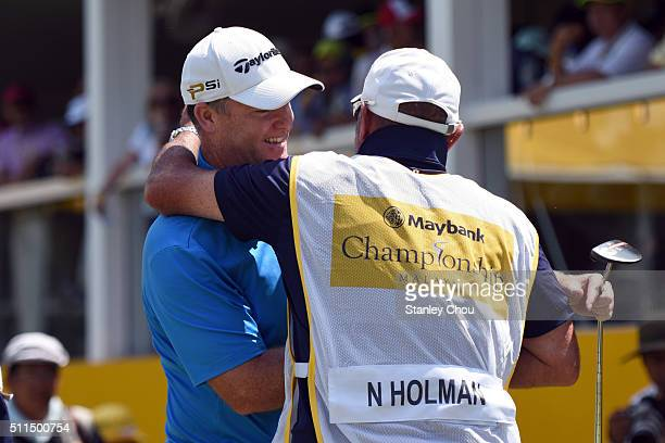 Marcus Fraser of Australia celebrates with Nathan Holman's caddie on the 18th hole during the fourth round of the Maybank Championship Malaysia at...