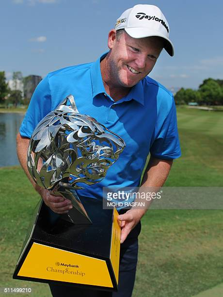 Marcus Fraser of Australia smiles as he poses with the trophy after winning the 2016 Maybank Malaysia Championship golf tournament in Kuala Lumpur on...
