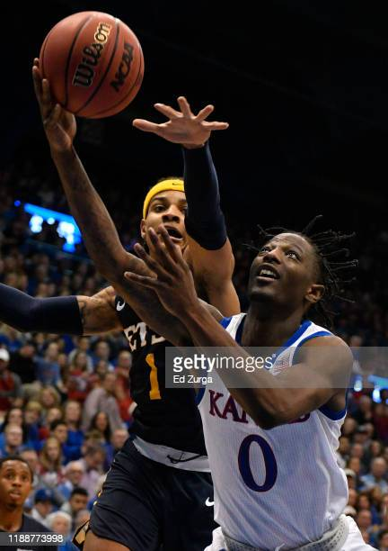 Marcus Garrett of the Kansas Jayhawks lays the ball up against Tray Boyd III of the East Tennessee State Buccaneers of the East Tennessee State...