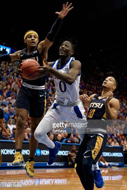Marcus Garrett of the Kansas Jayhawks lays the ball up against Tray Boyd III and Patrick Good of the East Tennessee State Buccaneers of the East...
