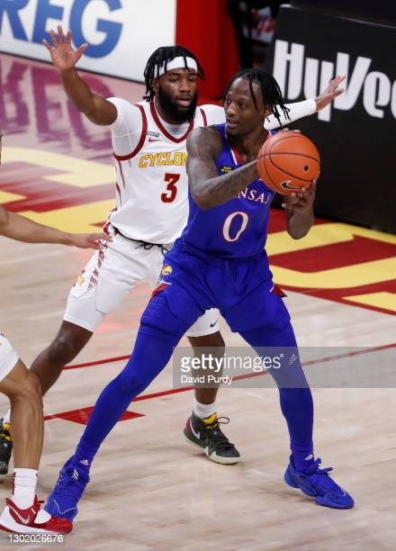 Marcus Garrett of the Kansas Jayhawks passes the ball as Tre Jackson of the Iowa State Cyclones defends in the first half of play at Hilton Coliseum...