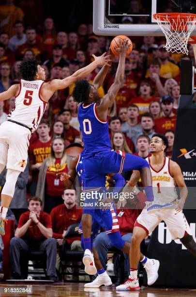 Marcus Garrett of the Kansas Jayhawks takes a shot as Lindell Wigginton of the Iowa State Cyclones and Nick WeilerBabb of the Iowa State Cyclones...
