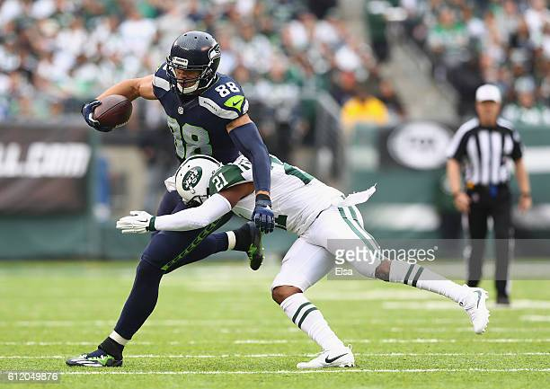 Marcus Gilchrist of the New York Jets attempts to tackle Jimmy Graham of the Seattle Seahawks in the third quarter at MetLife Stadium on October 2...