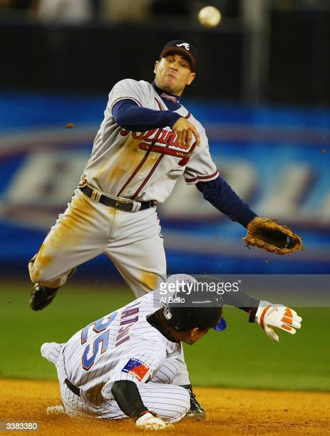 Marcus Giles of the Atlanta Braves turns a double play as Kazuo Matsui of the New York Mets slides into second base during their game on April 15,...