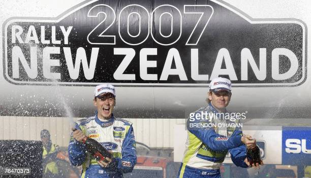 Marcus Gronholm and codriver Timo Rautiainen of Finland stand on their Ford Focus Rs as they celebrate victory in the Rally of New Zealand at the end...