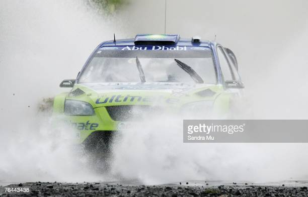 Marcus Gronholm of Finland and codriver Timo Rautiainen of Finland and the BP Ford World Rally team drive their Ford Focus RS through the water...