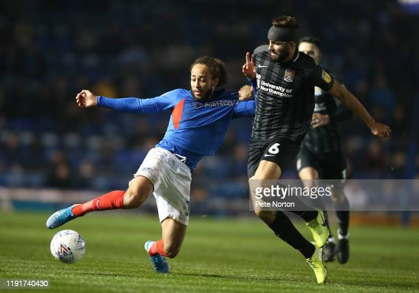 Marcus Harness of Portsmouth plays the ball under pressure from Jordan Turnbull of Northampton Town during the Leasingcom Trophy match between...