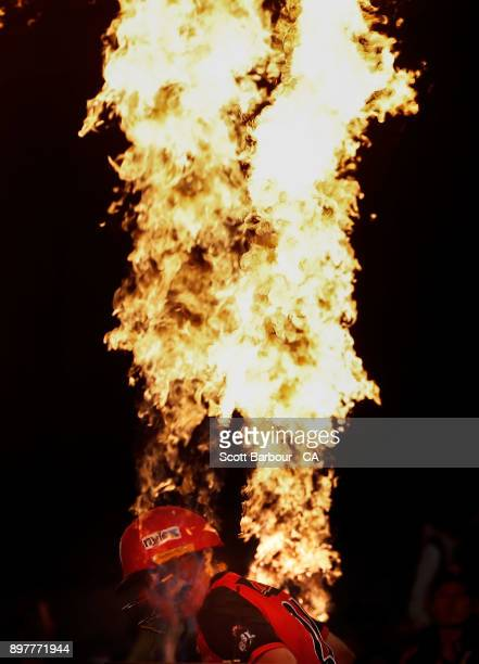 Marcus Harris of the Renegades walks out to bat through flames during the Big Bash League match between the Melbourne Renegades and the Brisbane Heat...