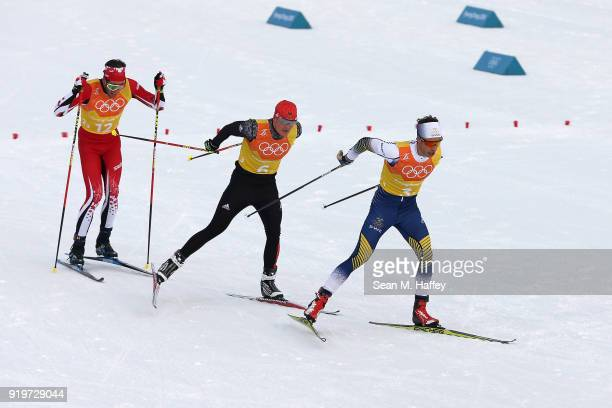 Marcus Hellner of Sweden Lucas Boegl of Germany and Russell Kennedy of Canada compete during CrossCountry Skiing men's 4x10km relay on day nine of...