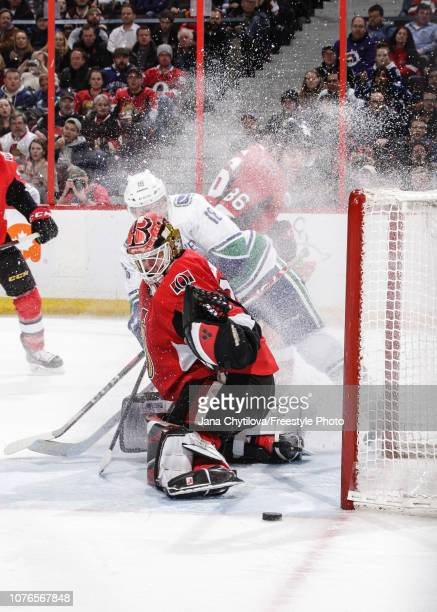 Marcus Hogberg of the Ottawa Senators makes a pas save against Jake Virtanen of the Vancouver Canucks as Christian Wolanin of the Ottawa Senators...