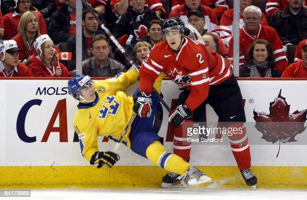 Marcus Johansson of Team Sweden is checked by Colten Teubert of Team Canada during the 2009 IIHF World Junior Championships held at Scotiabank Place...