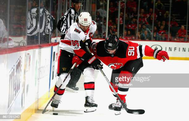 Marcus Johansson of the New Jersey Devils and Mike Hoffman of the Ottawa Senators battle for control of the puck during the game at Prudential Center...