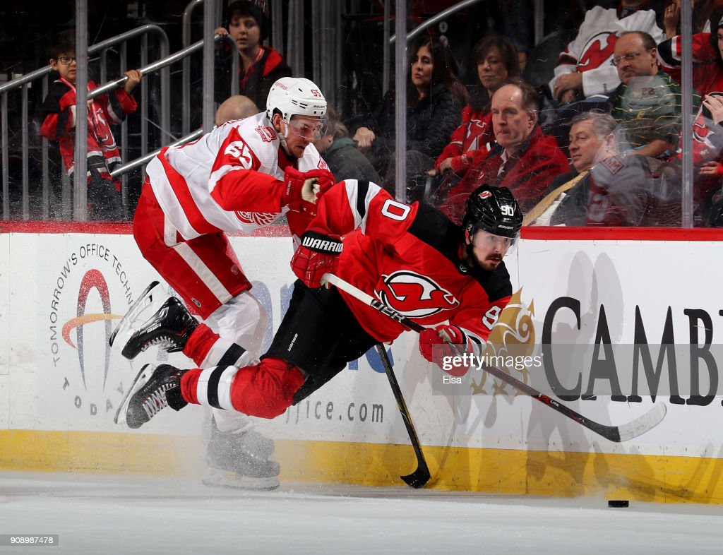 Marcus Johansson #90 of the New Jersey Devils is hit by Danny DeKeyser #65 of the Detroit Red Wings in the third period on January 22, 2018 at Prudential Center in Newark, New Jersey.