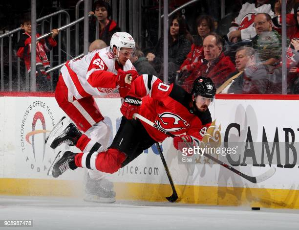 Marcus Johansson of the New Jersey Devils is hit by Danny DeKeyser of the Detroit Red Wings in the third period on January 22 2018 at Prudential...
