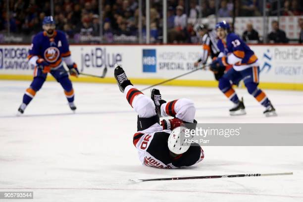 Marcus Johansson of the New Jersey Devils lies on the ice in the second period after being injured against the New York Islanders at Barclays Center...