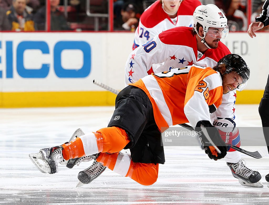 Marcus Johansson #90 of the Washington Capitals and Claude Giroux #28 of the Philadelphia Flyers collide in the first period at Wells Fargo Center on March 5, 2014 in Philadelphia, Pennsylvania.
