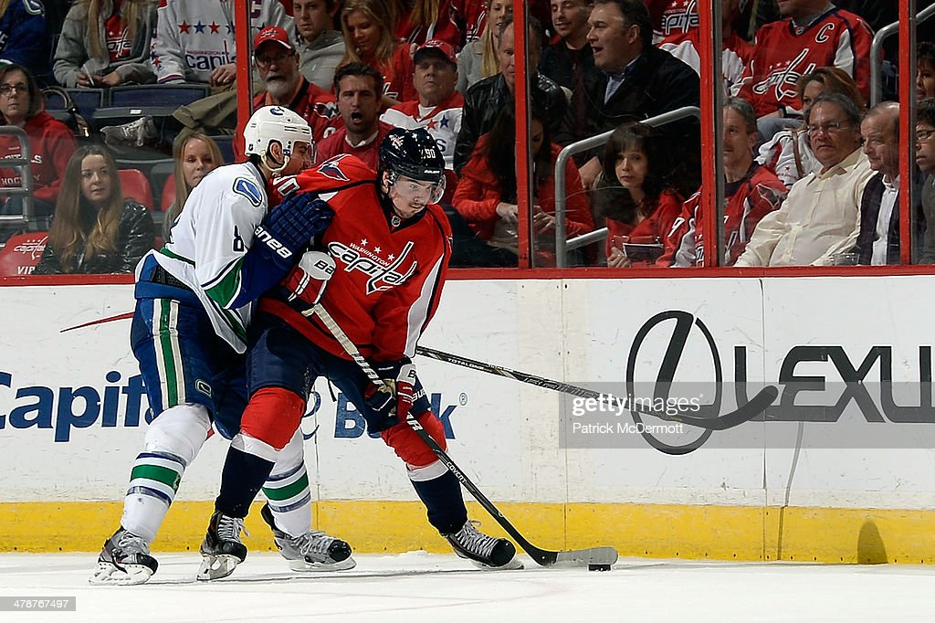 Marcus Johansson #90 of the Washington Capitals battles for the puck against Chris Tanev #8 of the Vancouver Canucks in the second period during an NHL game at Verizon Center on March 14, 2014 in Washington, DC.