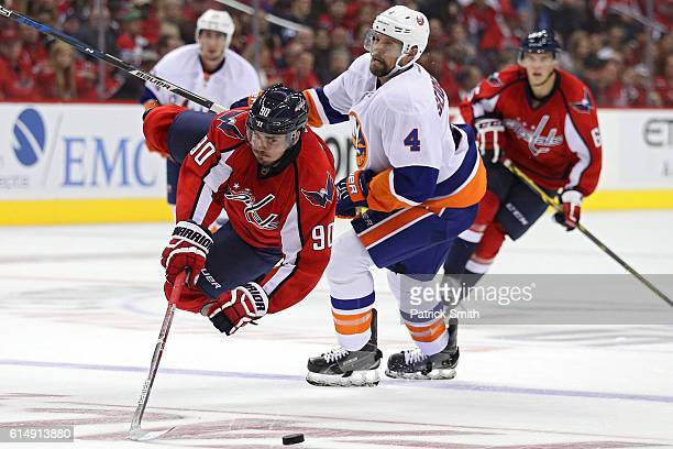 Marcus Johansson of the Washington Capitals is tripped by Dennis Seidenberg of the New York Islanders during the second period at Verizon Center on...