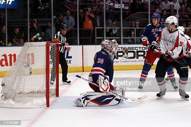 Marcus Johansson of the Washington Capitals scores a goal in the third period to tie the game 33 against goalie Henrik Lundqvist of the New York...