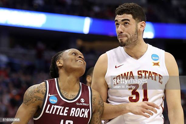 Marcus Johnson Jr #13 of the Arkansas Little Rock Trojans jokes with Georges Niang of the Iowa State Cyclones on in the first half during the second...