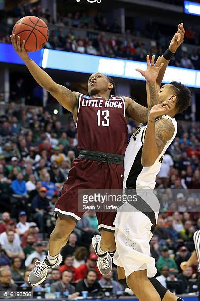 Marcus Johnson Jr #13 of the Arkansas Little Rock Trojans makes a shot over Vince Edwards of the Purdue Boilermakers during the first round of the...