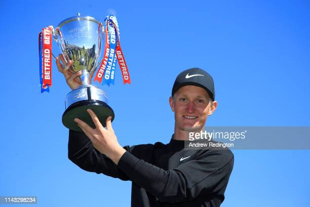 Marcus Kinhult of Sweden poses with the trophy following his victory during day four of the Betfred British Masters at Hillside Golf Club on May 12,...