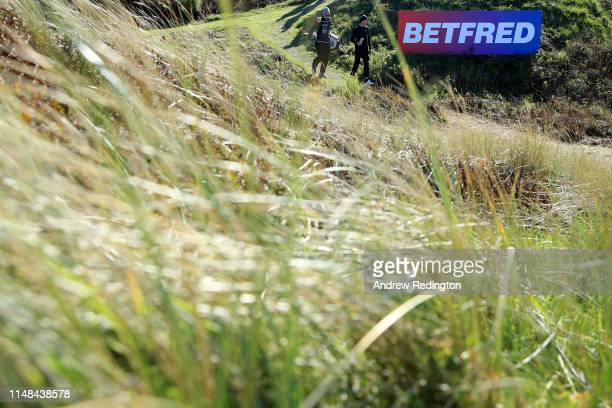 Marcus Kinhult of Sweden walks down the 18th hole with his caddie during day three of the Betfred British Masters at Hillside Golf Club on May 11...